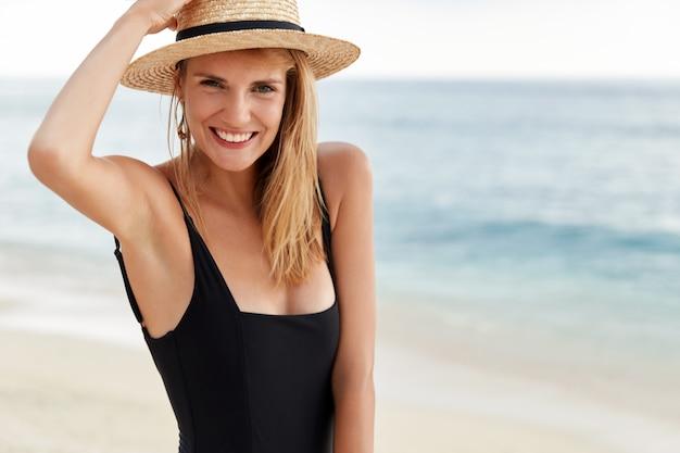 Taille-up portret van jonge schattige vrouwelijke reiziger in bikini en hoed ontdekt tropisch land, poseert aan de kustlijn van de oceaan, blij om zomervakantie in het buitenland door te brengen, heeft een positieve mooie uitdrukking.