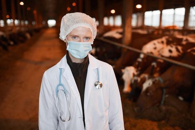 Taille-up portret van jonge vrouwelijke dierenarts camera kijken terwijl staande op melkveebedrijf, kopieer ruimte