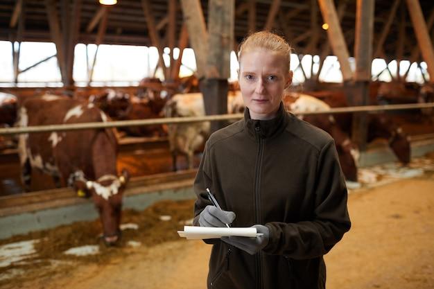 Taille-up portret van jonge vrouwelijke werknemer klembord houden en kijken naar camera terwijl staande in vee schuur op familieboerderij, kopie ruimte