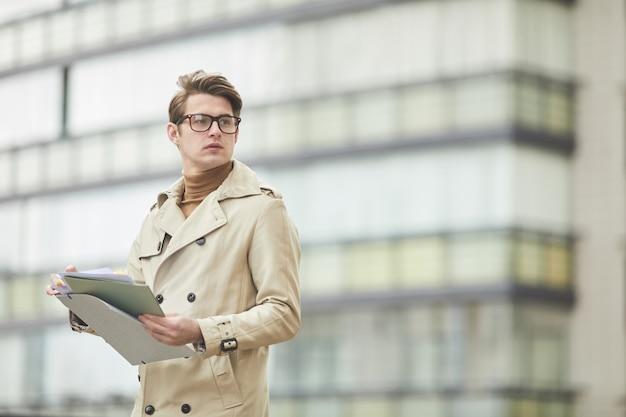 Taille-up portret van jonge zakenman dragen trenchcoat en klembord vasthouden terwijl buitenshuis staan en wegkijken in stedelijke stad omgeving, kopie ruimte