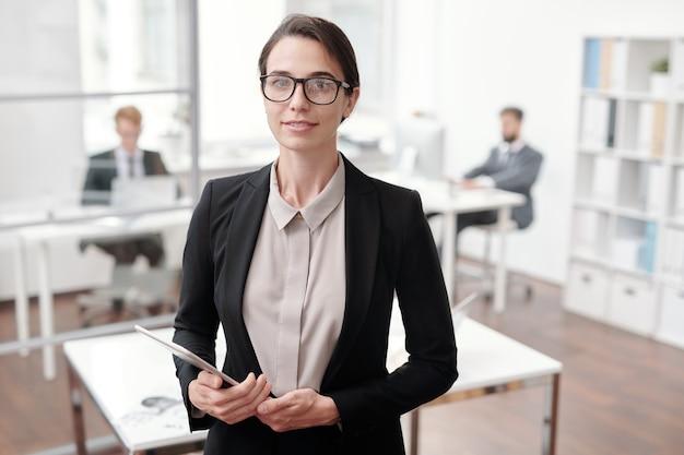 Taille-up portret van jonge zakenvrouw en digitale tablet vasthouden terwijl staande in kantoor, kopieer ruimte
