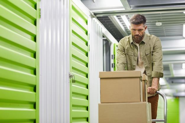 Taille-up portret van knappe bebaarde man kar met kartonnen dozen laden in self storage unit, kopieer ruimte