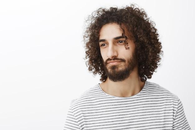 Taille-up portret van knappe mannelijke dromerige mannelijke ontwerper met krullend kapsel en stijlvol gestreept t-shirt, wegkijkend en sensueel glimlachend