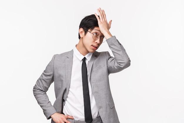 Taille-up portret van knappe vergeetachtige aziatische mannelijke werkgever, officemanager vergat iets kopen, voorhoofd slaan en wegzuchtend wegkijken, onthoud belangrijke taak op witte muur