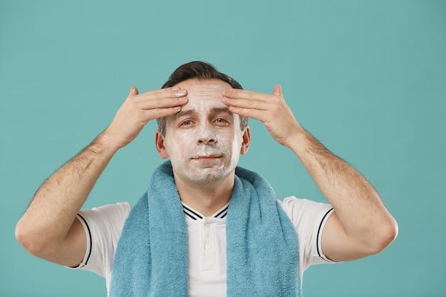 Taille-up portret van knappe volwassen man gezicht crème toe te passen