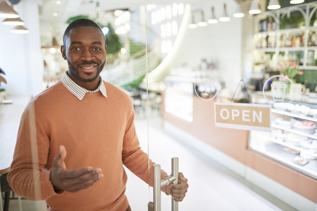 Taille-up portret van lachende adrian-amerikaanse man die 's ochtends café opent en gasten verwelkomt, kopieer ruimte