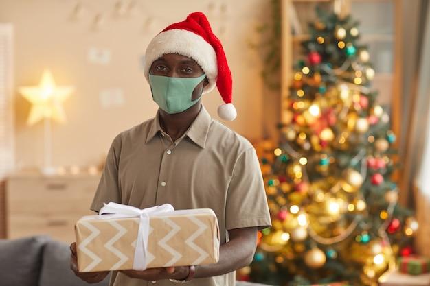 Taille-up portret van lachende afro-amerikaanse man kerstcadeau houden en masker dragen terwijl poseren in gezellig interieur, kopieer ruimte