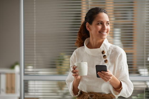 Taille-up portret van lachende elegante vrouw met koffiemok en smartphone terwijl u geniet van pauze van het werk, kopieer ruimte