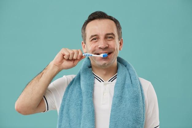 Taille-up portret van lachende man van middelbare leeftijd tanden poetsen