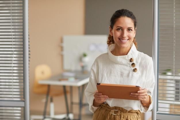 Taille-up portret van lachende succesvolle zakenvrouw camera kijken en digitale tablet te houden terwijl u werkt vanuit huis, kopieer ruimte