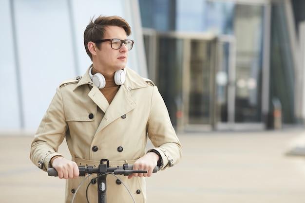 Taille-up portret van moderne jonge zakenman elektrische scooter rijden naar camera en wegkijken met stedelijke stadsgebouwen op achtergrond, kopieer ruimte