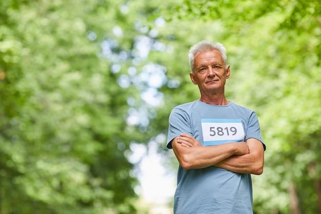 Taille-up portret van moderne kaukasische senior man die deelneemt aan de zomer marathon race staande in park met gekruiste armen kijken naar camera, kopieer ruimte