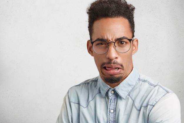 Taille-up portret van modieuze bebaarde man draagt een bril en shirt, heeft walging expressie