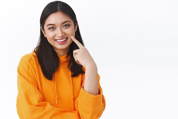 Taille-up portret van mooie aziatische vrouw in oranje hoodir, wijzend op wang of gezicht en glimlachen, huidverzorgingsbehandeling toepassen, koreaanse make-up, staande witte muur