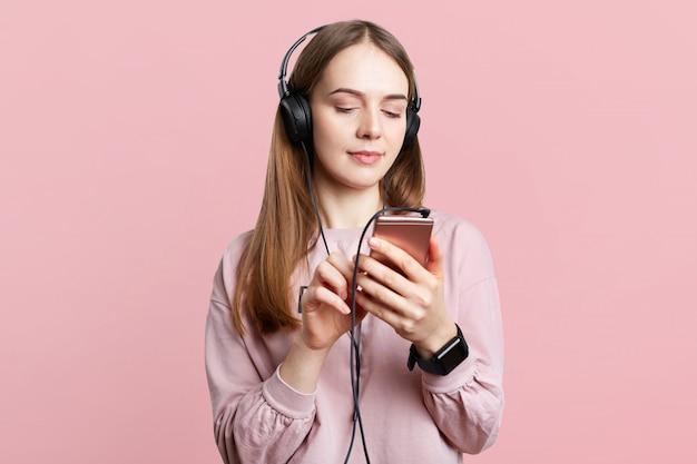 Taille-up portret van mooie brunette vrouw draagt een koptelefoon, controleert lied uit afspeellijst