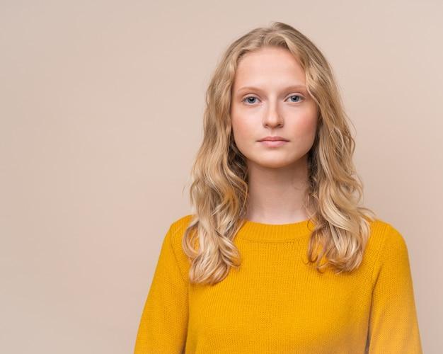 Taille-up portret van mooie jonge ernstige slimme blonde scandinavische vrouw zonder make-up op beige muur. vrouw met fris gezicht en krullend haar in felgele trui, tiener in oranje trui