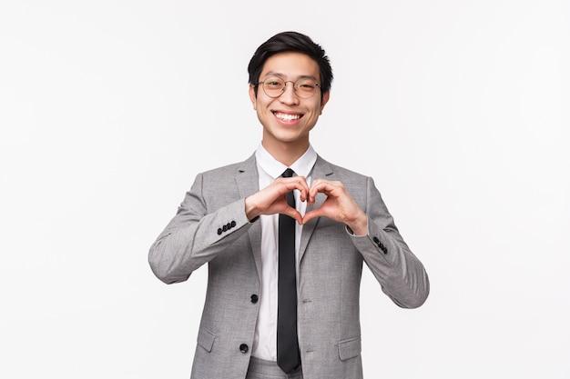 Taille-up portret van mooie, schattige aziatische jonge man, officemanager in pak, met hartteken en glimlachend blozend, uiting geven aan zijn medeleven, in liefde bekennen, staande op een witte muur
