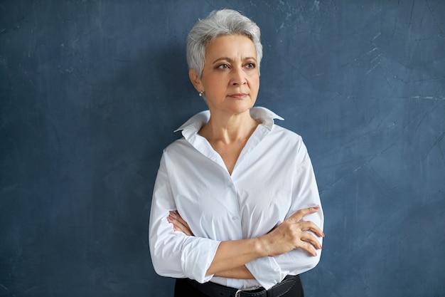 Taille-up portret van mooie succesvolle grijze haren rijpe zakenvrouw in formele slijtage met ernstige peinzende gezichtsuitdrukking
