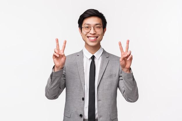 Taille-up portret van optimistische vrolijke en knappe aziatische man in grijs pak, bril met vredestekens, lachende kawaii, gekke foto, blij en vrolijk op witte muur