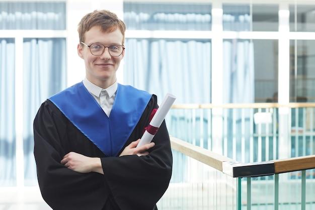 Taille-up portret van roodharige jonge man die afstudeerjurk draagt en diploma vasthoudt terwijl hij met gekruiste armen in het moderne universiteitsinterieur staat en naar de camera glimlacht, kopieer ruimte