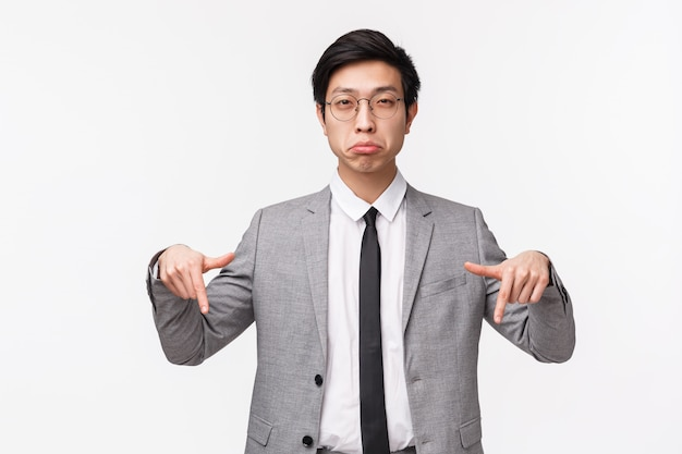 Taille-up portret van sceptische, achterdochtige aziatische man in pak, officemanager loensen van ongeloof naar, iemand beoordelen, wijzende vinger naar iets twijfelachtigs, op een witte muur