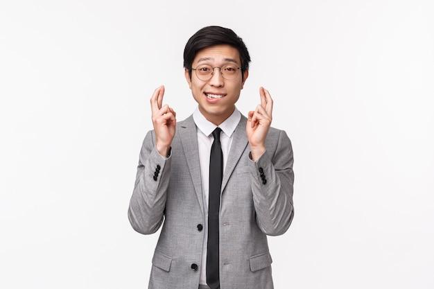 Taille-up portret van schattige hoopvolle aziatische man, officemanager hoop verhoging of promotie te krijgen, kruis vingers geluk en bijten lip bidden, smekend om wens uit te laten komen, staand op witte muur