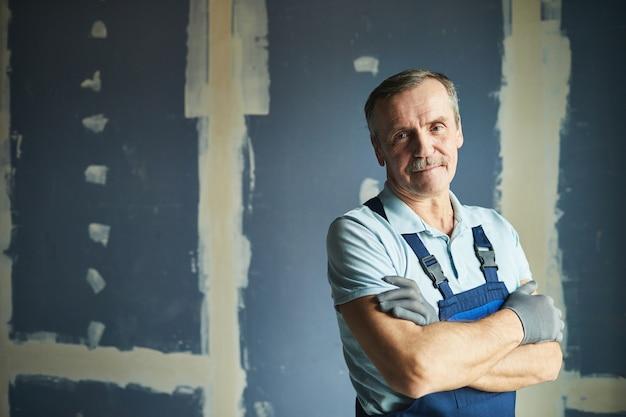 Taille-up portret van senior bouwvakker glimlachend in de camera terwijl vol vertrouwen poseren tegen droge muur, kopieer ruimte