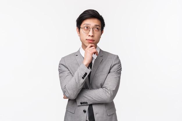 Taille-up portret van slimme en creatieve jonge aziatische mannelijke ondernemer in grijs pak, plan maken, hand op kin houden en nadenkend opzoeken, nadenkend over project, staand op witte muur