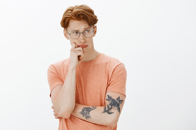 Taille-up portret van slimme en knappe roodharige man in glazen op zoek attent, denken