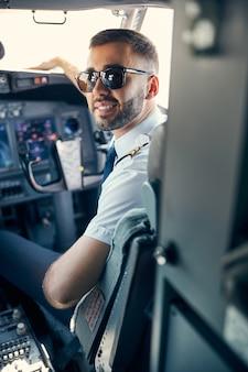Taille-up portret van stijlvolle piloot zittend op de stoel terwijl hij poseert voor de fotocamera