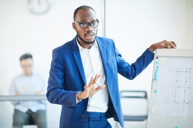 Taille-up portret van succesvolle afro-amerikaanse zakenman permanent door whiteboard tijdens het presenteren van ontwerpproject tijdens bijeenkomst in kantoor, kopieer tempo