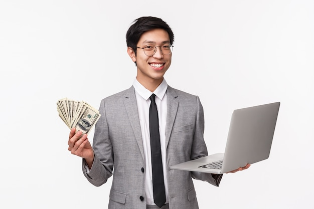 Taille-up portret van succesvolle rijke aziatische zakenman, it-programmeur verkopen applicatie