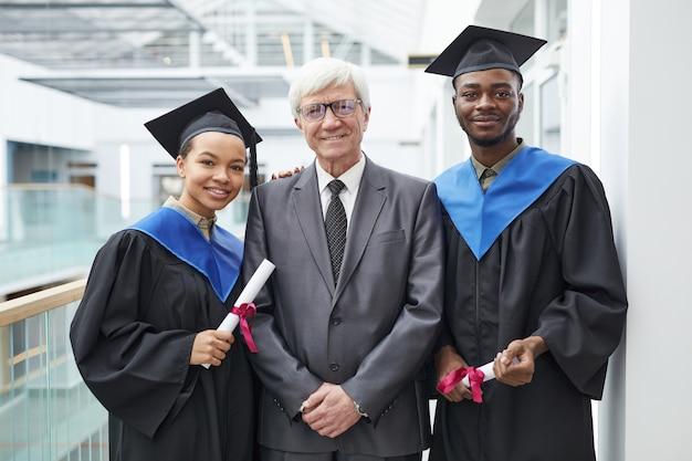 Taille-up portret van twee afgestudeerden met diploma's terwijl ze poseren met een volwassen professor en glimlachen naar de camera