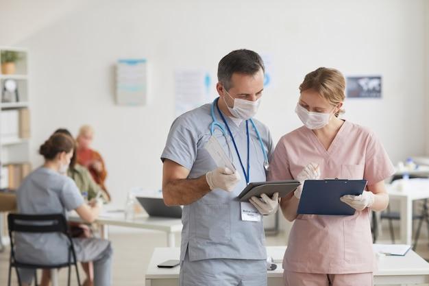 Taille-up portret van twee artsen die maskers dragen en praten terwijl ze naar een tablet in de medische kliniek kijken, kopieer ruimte