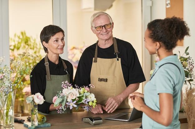 Taille-up portret van twee bloemisten die met de klant praten in de kopieerruimte van de bloemenwinkel