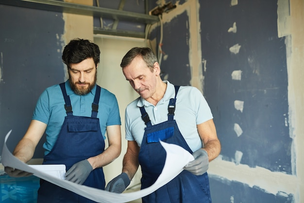 Taille-up portret van twee bouwvakkers die plannen houden en tegen de droge muur staan tijdens het renoveren van huis, kopie ruimte