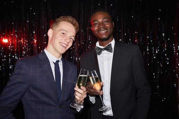 Taille-up portret van twee elegante jonge mannen met champagneglazen en lachend naar de camera terwijl staande tegen sprankelende achtergrond op feestje, geschoten met flits