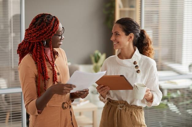 Taille-up portret van twee succesvolle jonge zakenvrouwen documenten bespreken en vrolijk glimlachen terwijl staande in modern kantoor interieur, kopieer ruimte