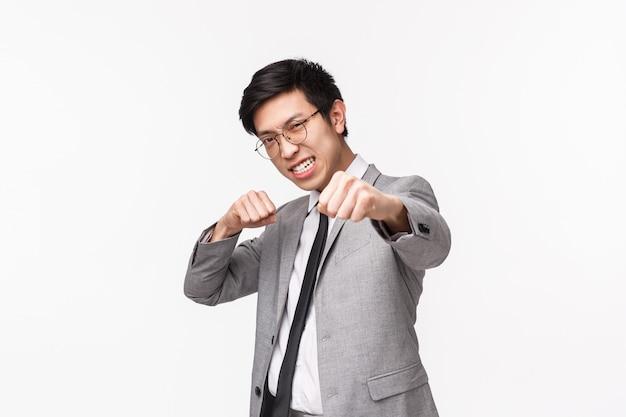 Taille-up portret van vastberaden, zelfverzekerde knappe aziatische zakenman, vergroot zelfvertrouwen in de buurt van spiegel die in bokshouding staat met opgeheven gebalde vuisten en ernstig grimas, ponsen lucht