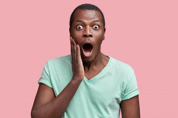 Taille-up portret van verbaasd afgeluisterde ogen donkere huid man in casual t-shirt, verrast om schokkend nieuws te horen, geïsoleerd over roze
