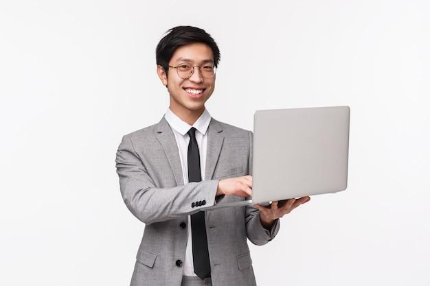 Taille-up portret van vertrouwen succesvolle jonge aziatische man in grijs pak
