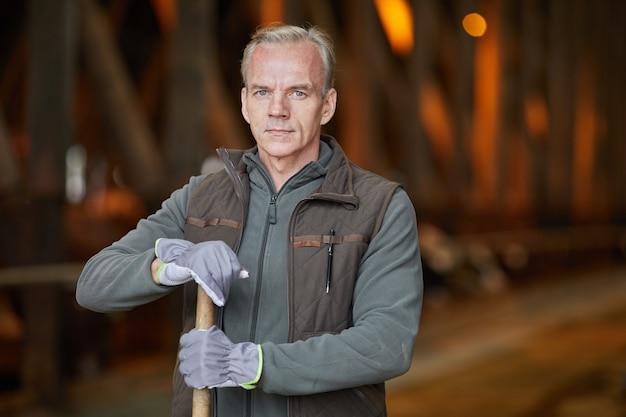 Taille-up portret van volwassen landarbeider camera kijken tijdens het schoonmaken van de koeienstal op familieboerderij, kopie ruimte