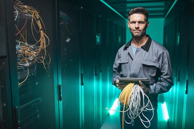 Taille-up portret van volwassen netwerkingenieur die naar camera kijkt en digitale tablet gebruikt in serverruimte tijdens onderhoudswerkzaamheden in datacenter, kopieer ruimte
