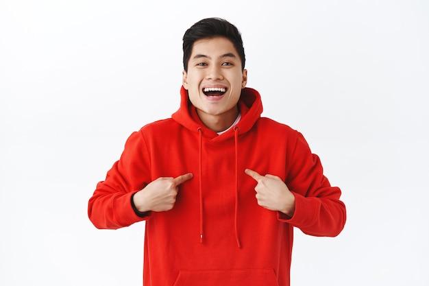 Taille-up portret van vrolijke, zelfverzekerde jonge aziatische man die vraagt om deel te nemen aan het evenement, zichzelf trots en tevreden wijzend, glimlachend, kampioen wordend, pratend over persoonlijke prestatie.