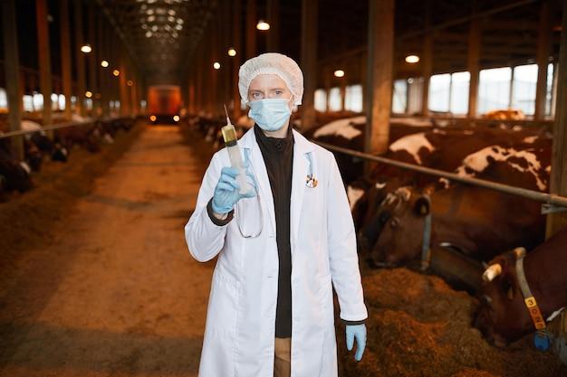 Taille-up portret van vrouwelijke dierenarts die grote spuit met geneeskunde houdt tijdens het vaccineren van koeien en vee op de boerderij, kopie ruimte