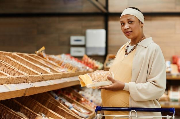 Taille-up portret van zwangere afro-amerikaanse vrouw die vers brood koopt terwijl ze boodschappen doet in de supermarkt, kopieer ruimte