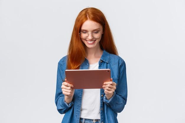 Taille-up portret vrij gelukkige roodharige vrouwelijke student, studeren, werken aan ontwerpproject, bril dragen, digitale tablet vasthouden en tevreden gadgetscherm kijken, tevreden glimlachen.