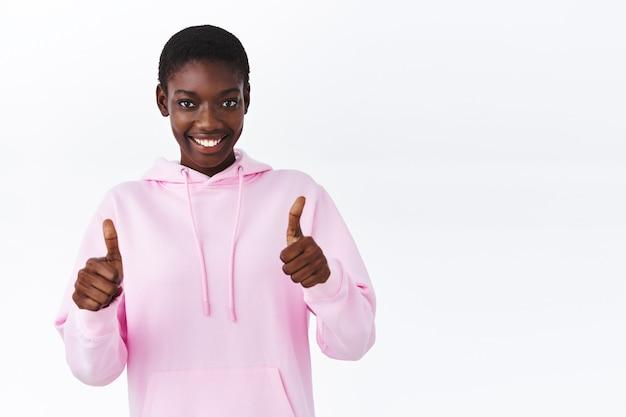 Taille-up portret zelfverzekerde afro-amerikaanse vrouw in roze hoodie moedigt je aan om een keuze te maken, prijs je prestatie