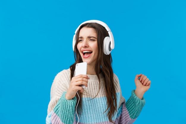 Taille-up portret zorgeloos knappe jonge brunette vrouw karaoke spel op telefoon spelen