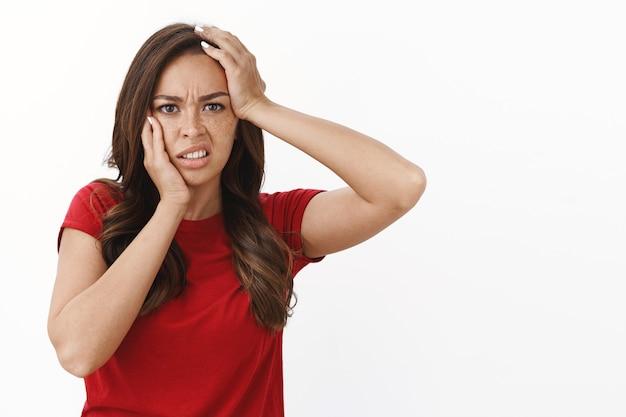 Taille-up shot beschaamd hopeloze jonge brunette vrouw in rood casual t-shirt grijpt het hoofd, fronst overstuur en krimpt ineen van teleurstelling, verliest concurrentie gevoel frustratie en verdriet